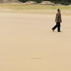 一个游人行走在沙滩上