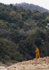 一位僧人走下岩石坡